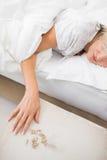 Femme dormant dans le lit avec des pilules dans le premier plan Photo libre de droits