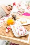 Femme dormant dans le lit avec le plateau de petit déjeuner près de elle Image stock