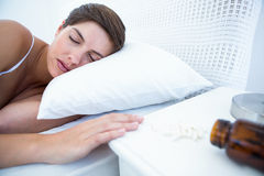 Femme dormant dans le lit par la bouteille renversée de pilules Images stock