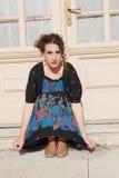Femme déprimée et agitated se tapissant devant la maison à Photographie stock