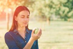 Femme drôle blonde assez jeune mangeant la pomme extérieure sur la rue Image libre de droits