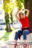 Femme drôle s'asseyant sur le banc en parc et écoutant la musique Photographie stock libre de droits