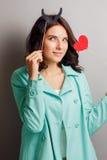 Femme drôle avec des klaxons tenant un coeur Images libres de droits