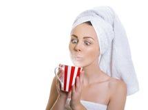 Femme drôle enveloppée dans une serviette buvant du thé chaud Images libres de droits