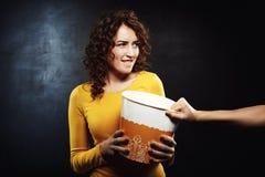 Femme drôle essayant d'obtenir le maïs éclaté avec des amis tout en observant le film Photo libre de droits