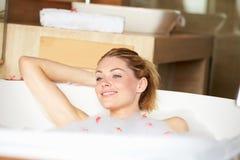 Femme détendant dans le bain moussant Photos stock