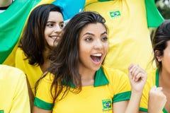 Femme du Brésil avec d'autres fans de foot brésiliens au stade image stock
