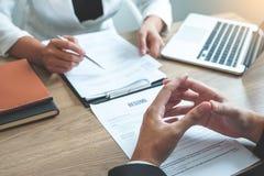 Femme du cadre supérieur lisant un résumé pendant un demandeur et un recrutement de réunion de jeune homme des employés d'entrevu image libre de droits