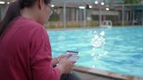 Femme effectuant le paiement en ligne avec la carte de crédit et le smartphone près de la piscine clips vidéos