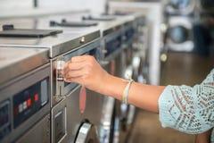 Femme effectuant le paiement mettant le quart à la machine de lavage de laverie automatique dans la blanchisserie publique Photographie stock