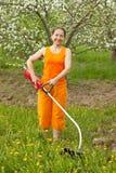 Femme effectuant le travail dans son jardin avec la herbe-faucheuse Photographie stock