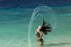 Femme effleurant ses longs cheveux à photo libre de droits