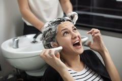 Femme effrayée dans un salon de coiffure images libres de droits
