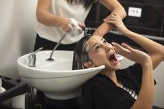Femme effrayée dans un salon de coiffure image stock