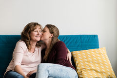 Femme embrassé par sa fille affectueuse Photos stock