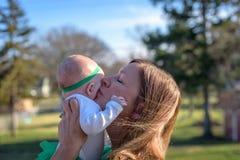 Femme embrassant le bébé le jour du ` s de St Patrick photographie stock