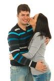 Femme embrassant sa joue d'ami Photos stock