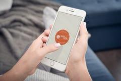 Femme employant Couchsurfing APP sur l'iPhone 8 d'Apple plus Photos stock