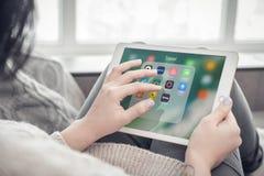 Femme employant des apps de voyage sur un iPad tout neuf d'Apple pro photos libres de droits