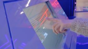 Femme employant l'affichage interactif d'écran tactile à l'exposition de technologie