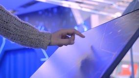 Femme employant l'affichage interactif d'écran tactile à l'exposition moderne de technologie