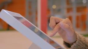 Femme employant l'affichage interactif d'écran tactile à l'exposition urbaine