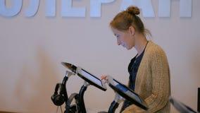 Femme employant l'affichage interactif d'écran tactile au musée d'histoire moderne