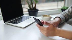 Femme employant l'APP sur le smartphone en café potable de café souriant et textotant au téléphone portable Belle jeune femelle banque de vidéos