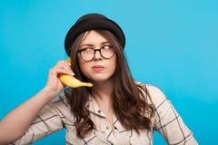 Femme employant la banane en tant que téléphone Photographie stock libre de droits