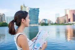 Femme employant la carte de ville dans Macao Photos libres de droits