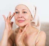 Femme employant la crème de visage image libre de droits