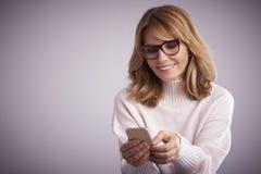 Femme employant la messagerie textuelle de téléphone portable et photos libres de droits