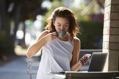 Femme employant le café potable de smartphone et d'ordinateur portable dehors Image libre de droits