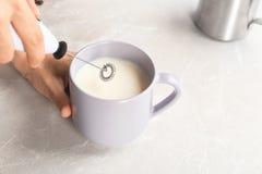 Femme employant le frother de lait dans la tasse photographie stock libre de droits