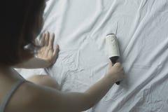 Femme employant le lit propre de roulement collant La jeune fille enlèvent des cheveux As photos libres de droits