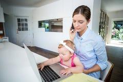 Femme employant le téléphone portable et le bébé jouant avec l'ordinateur portable Photos libres de droits