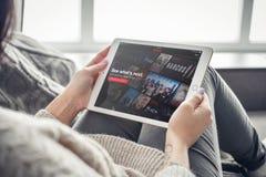 Femme employant Netflix APP sur un iPad tout neuf d'Apple pro photographie stock libre de droits