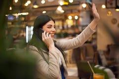 Femme employant parler au téléphone portable au café Photo libre de droits