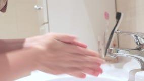 Femme employant un dispencer de solution de nettoyage, fand de savon liquide lavant son robinet de mains, ouvert et étroit d'eau banque de vidéos