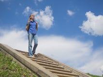 Femme en bas des escaliers contre le ciel bleu photo stock
