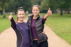 Femme en bonne santé au parc montrant des pouces  Photographie stock