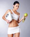 Femme en bonne santé avec les échelles et la pomme verte. Images libres de droits