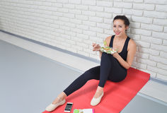 Femme en bonne santé convenable dans les vêtements de sport mangeant d'une salade fraîche après séance d'entraînement de forme ph Photo libre de droits