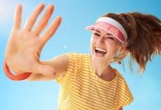 Femme en bonne santé dans la chemise jaune contre très haut dans le ciel cinq bleus images libres de droits