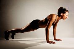 Femme en bonne santé de forme physique faisant un Pushup Photos stock
