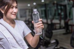 Femme en bonne santé de sport regardant l'eau de boissons image stock