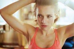 Femme en bonne sant? de sports dans la maison moderne ajustant des cheveux image libre de droits