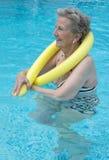 Femme en bonne santé et plus âgée s'exerçant dans la piscine Photos stock