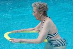 Femme en bonne santé et plus âgée s'exerçant dans la piscine Photographie stock