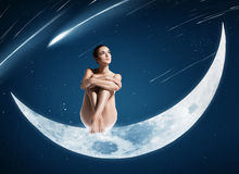 Femme en bonne santé s'asseyant sur la lune brillante Photo stock
